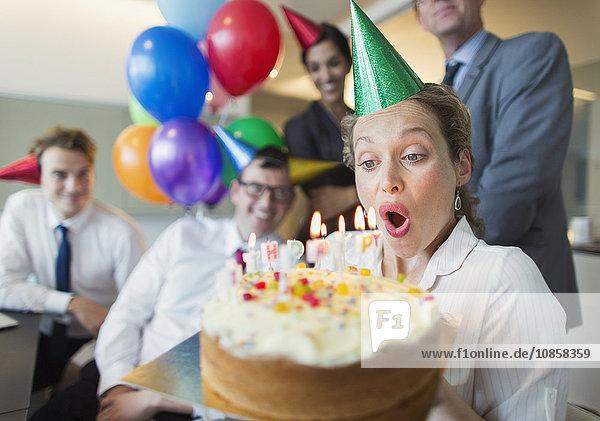 Kollegen beobachten Geschäftsfrau beim Ausblasen von Geburtstagskuchenkerzen