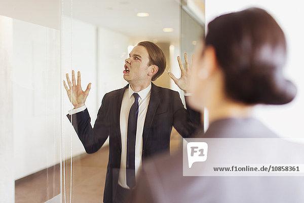 Dummer Geschäftsmann drückt Gesicht gegen Büroglas