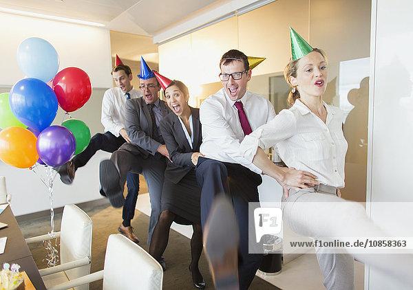 Verspielte Geschäftsleute mit Partyhüten tanzen in Conga-Linie