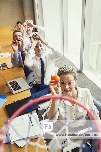 Geschäftsleute  die Plastikbälle auf Basketballkorb im Konferenzraum zielen
