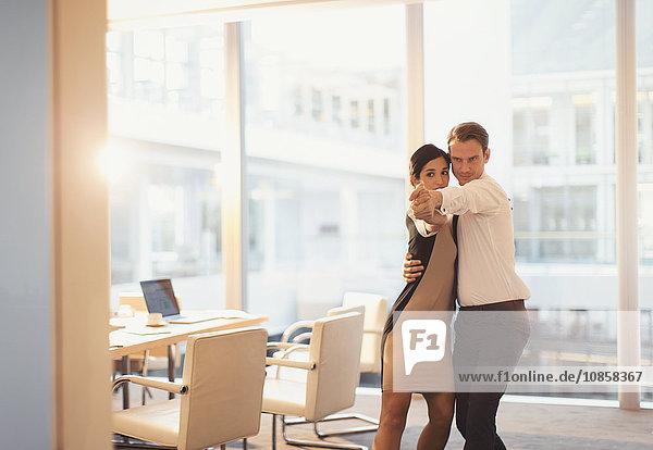 Geschäftsmann und Geschäftsfrau beim Tanzen im Konferenzraum