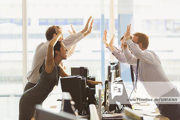 Überschwängliche Geschäftsleute  die sich über Computer im Büro freuen.