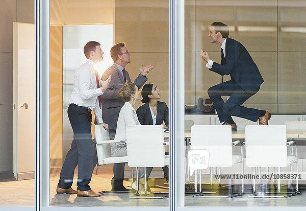 Überschwänglicher Geschäftsmann  der mit den Fäusten auf dem Konferenztisch sitzt.