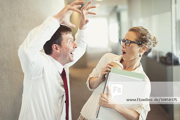 Geschäftsmann macht knurrende Geste bei verängstigter Geschäftsfrau