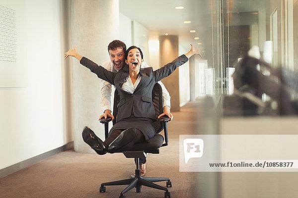 Verspielter Geschäftsmann schiebt überschwängliche Geschäftsfrau im Bürostuhl den Flur hinunter