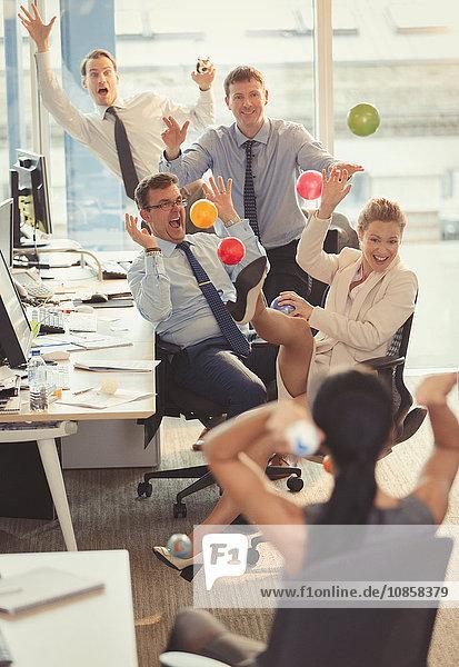 Verspielte Geschäftsleute  die sich im Büro mit bunten Plastikbällen bewerfen.