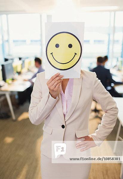 Porträt einer Geschäftsfrau mit Smiley-Gesichtsausdruck über dem Gesicht im Büro
