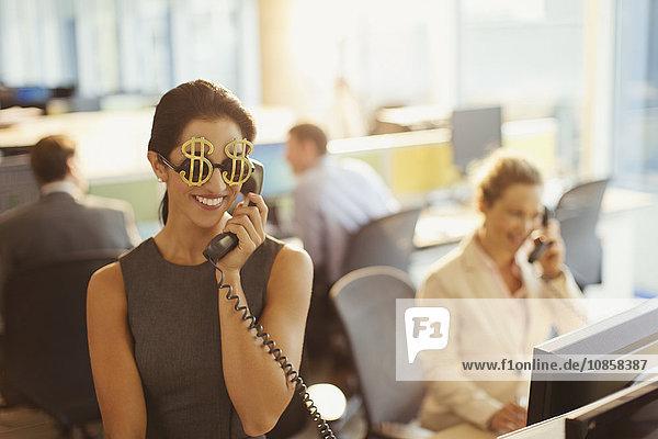 Porträt einer lächelnden Geschäftsfrau mit Dollarzeichen-Sonnenbrille am Telefon im Büro
