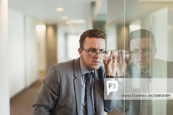 Fokussierter Geschäftsmann lauscht mit Glas im Büroflur