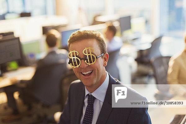 Portrait lächelnder Geschäftsmann mit Dollarzeichen-Sonnenbrille im Büro