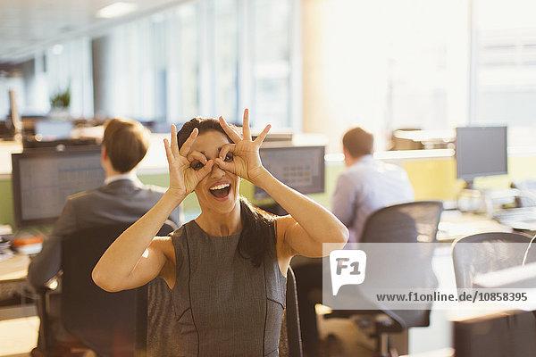 Porträt einer verspielten Geschäftsfrau  die vorgibt  im Büro eine Brille zu tragen.