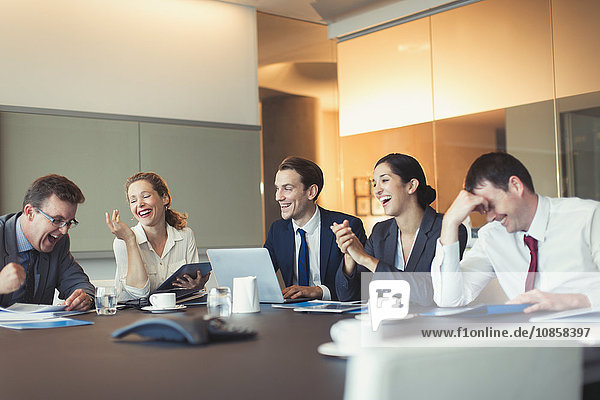 Business people laughing in conference room meeting