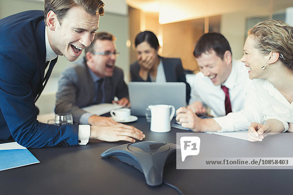 Lachende Geschäftsleute bei einer Telefonkonferenz im Konferenzraum
