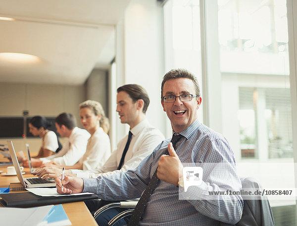 Porträt eines selbstbewussten Geschäftsmannes mit Daumen nach oben in der Konferenzraumbesprechung