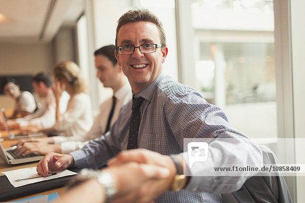 Portrait lächelnder Geschäftsmann beim Händeschütteln im Konferenzsaal