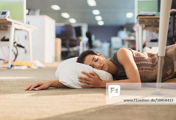 Geschäftsfrau schläft mit Kissen im Bürogeschoss
