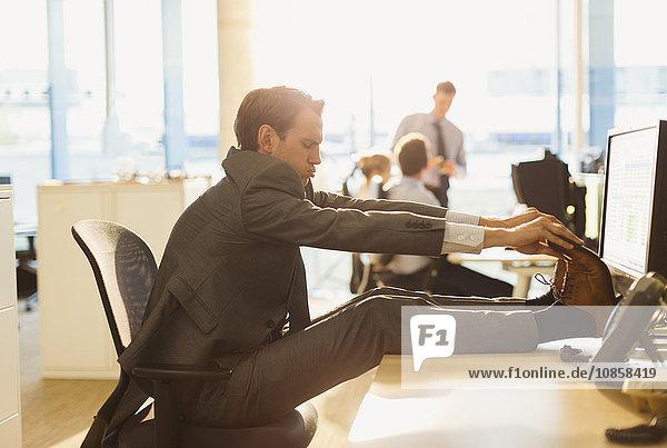 Geschäftsmann streckt Füße auf den Schreibtisch im Büro