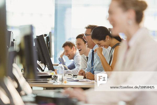 Geschäftsleute lachen am Schreibtisch im Büro