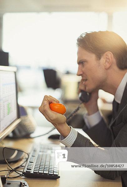Wütender Geschäftsmann quetscht Stressball und telefoniert am Computer im Büro.