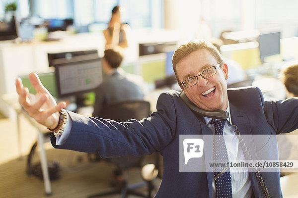 Porträt eines üppigen Geschäftsmannes mit ausgestreckten Armen beim Telefonieren