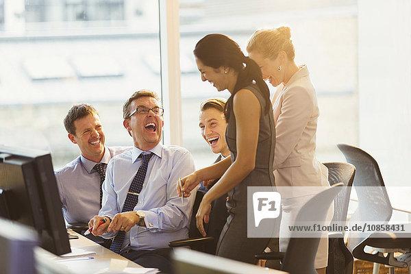Lachende Geschäftsleute am Computer im Büro