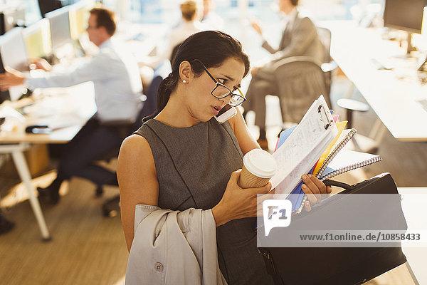 Gestresste Geschäftsfrau kämpft mit Multitasking im Büro