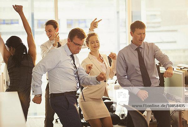 Begeisterte Geschäftsleute beim Feiern und Tanzen im Büro