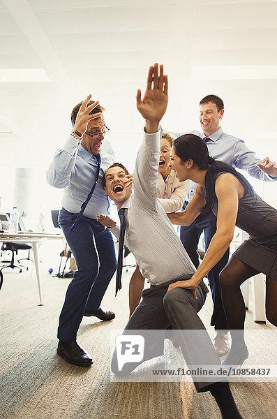Ausgelassene Geschäftsleute beim Feiern und Tanzen im Büro