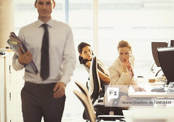 Geschäftsfrauen beim Auschecken von vorbeifahrenden Geschäftsleuten im Büro