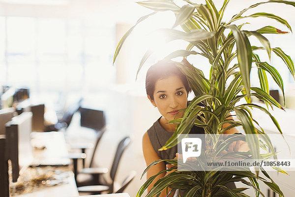 Porträt einer Geschäftsfrau  die sich hinter einer Fabrik im Büro versteckt hält.
