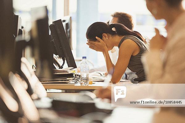 Gestresste Geschäftsfrau mit Kopf in den Händen am Schreibtisch