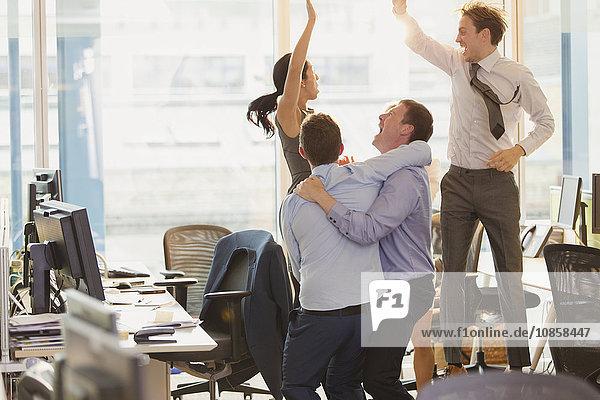 Überschwängliche Geschäftsleute beim Feiern und Springen im Büro