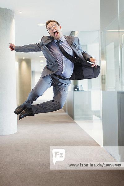 Überschwänglicher Geschäftsmann springt vor Freude in den Büroflur