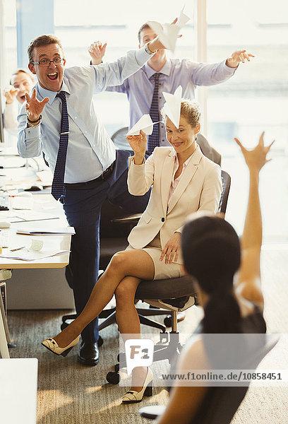 Verspielte Geschäftsleute  die sich im Büro mit Papierflugzeugen bewerfen.