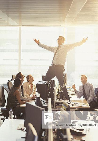 Kollegen beobachten ausgelassene Geschäftsleute  die auf Schreibtischen im Büro feiern.