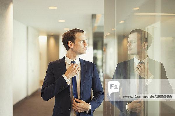 Zuversichtlicher Geschäftsmann beim Anpassen der Krawatte im Büroflur