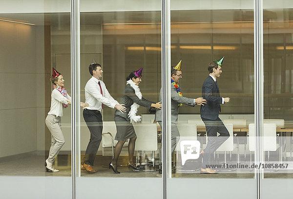 Geschäftsleute mit Partyhüten tanzen in Conga-Linie am Fenster des Konferenzraumes