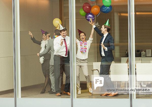 Geschäftsleute mit Partyhüten und Ballontänzen am Fenster des Konferenzraums