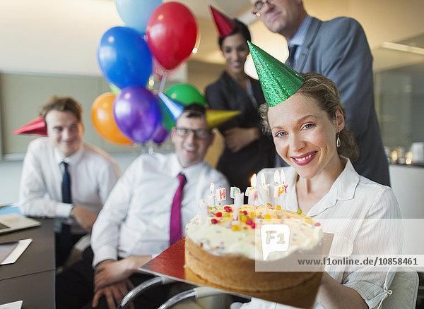 Portrait lächelnde Geschäftsfrau hält Geburtstagskuchen mit Kollegen im Hintergrund