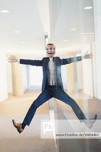 Symmetrisches Reflexionsporträt eines Geschäftsmannes mit ausgestreckten Armen und Beinen im Büroflur