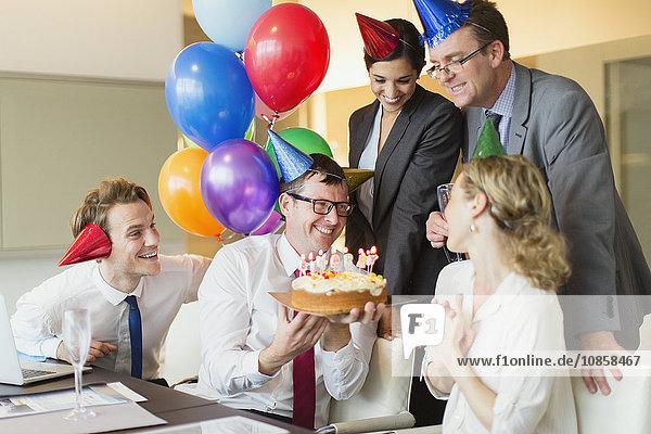 Kollegen präsentieren Geschäftsfrau mit Geburtstagskuchen im Konferenzraum