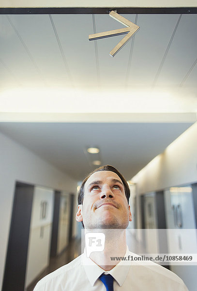 Geschäftsmann schaut auf den Pfeil über Kopf