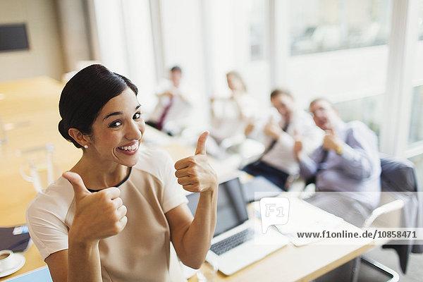 Porträt einer selbstbewussten Geschäftsfrau und Kollegen mit Daumen nach oben im Konferenzraum