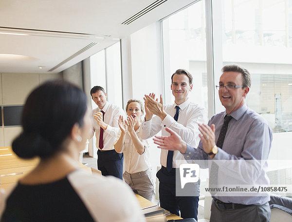 Geschäftsleute klatschen für Geschäftsfrau im Konferenzraum