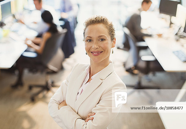 Portrait of confident businesswoman with arms crossed in office