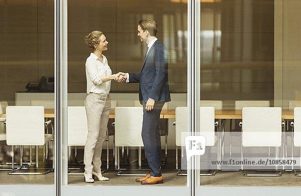 Geschäftsmann und Geschäftsfrau beim Händeschütteln am Konferenzraumfenster