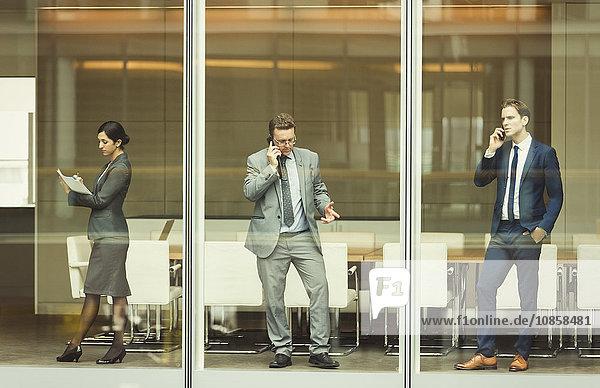 Geschäftsleute auf Handys und Notizen am Fenster des Konferenzraums