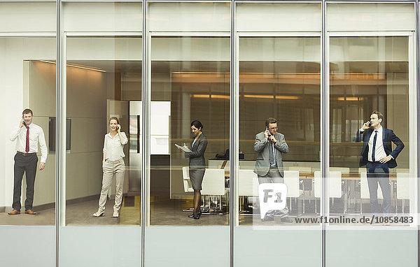 Geschäftsleute sprechen über Handys und überprüfen den Papierkram am Fenster des Konferenzraumes