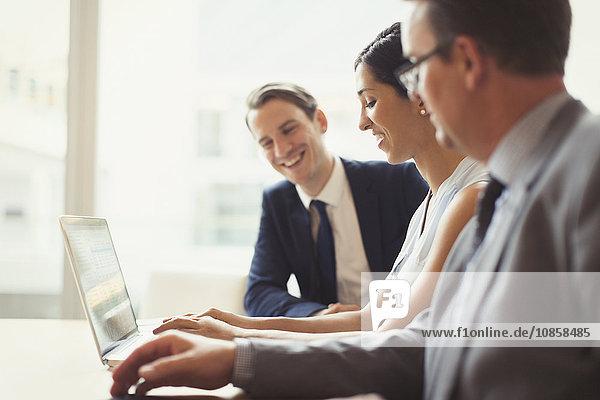 Lächelnde Geschäftsleute mit Laptop im Konferenzraum