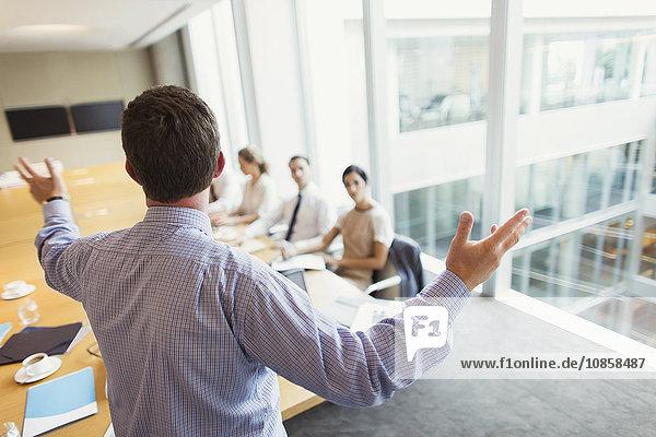 Geschäftsmann gestikuliert zu Kollegen in Konferenzraumbesprechung